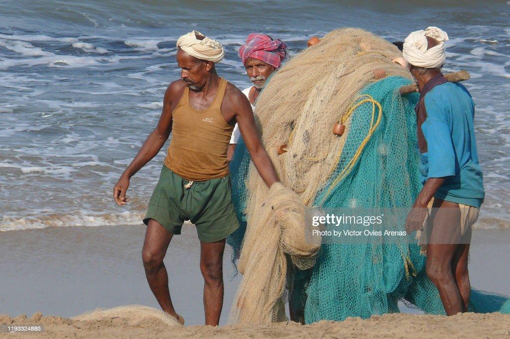 Three old local fishermen carrying their fishing nets on the beach in Gokarna, Karnataka, India : ストックフォト