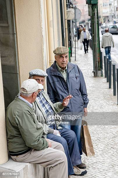Three old men discussing on the corner of street