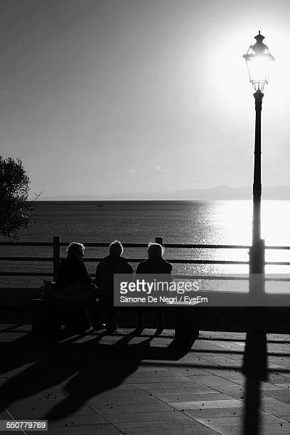 Three Old Men Sitting On Bench Looking At Sea