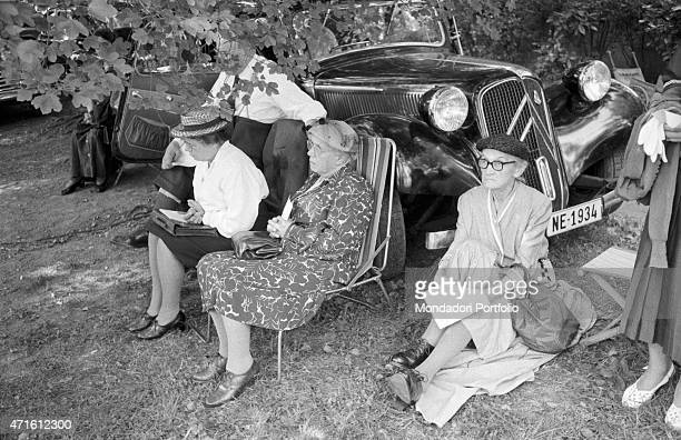 'Three old women listening to American preacher Billy Graham delivering a sermon The city houses the Geneva Summit discussing issues about security...