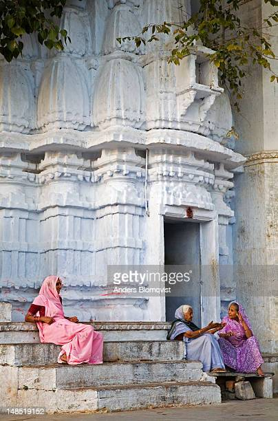 three old women sitting and talking by small temple at gangaur ghat. - gangaur stock pictures, royalty-free photos & images