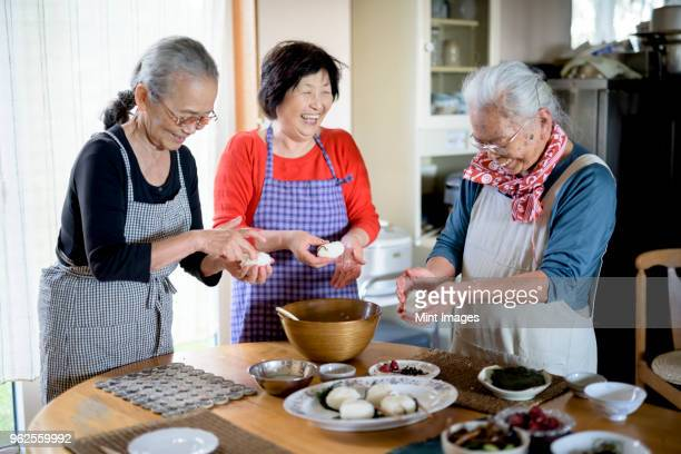 Three older women standing round a table in a kitchen, making sushi.