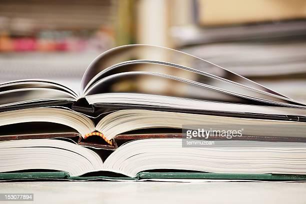 Drei offene Bücher liegen auf einem anderen