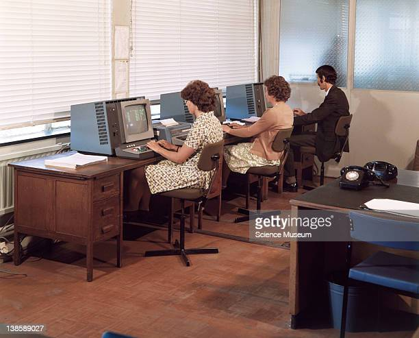 Three operators working at VDU terminals in the offices of International Computers Limited in Stevenage Hertfordshire