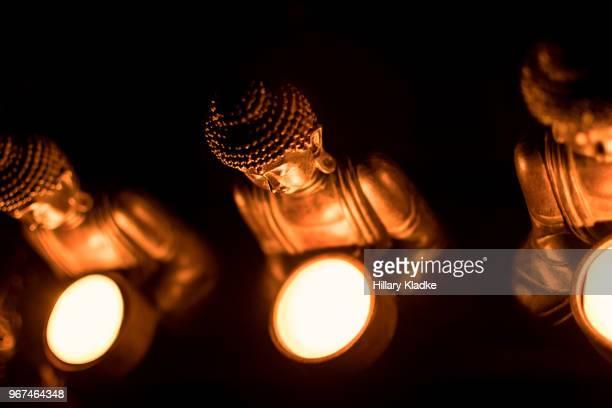 Three orange religious Buddha statues