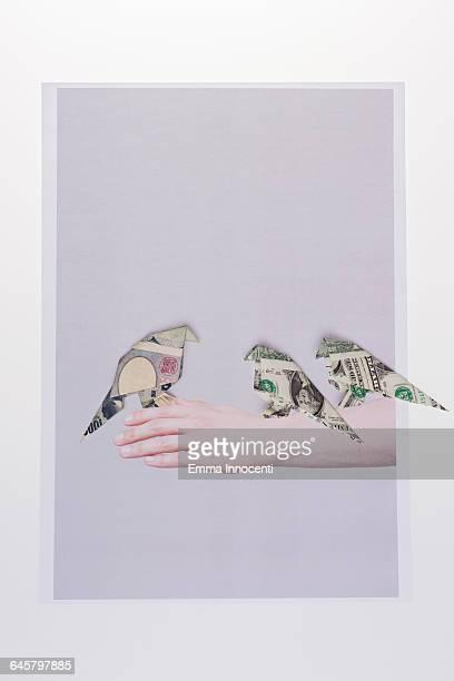Three origami birds sitting on hand