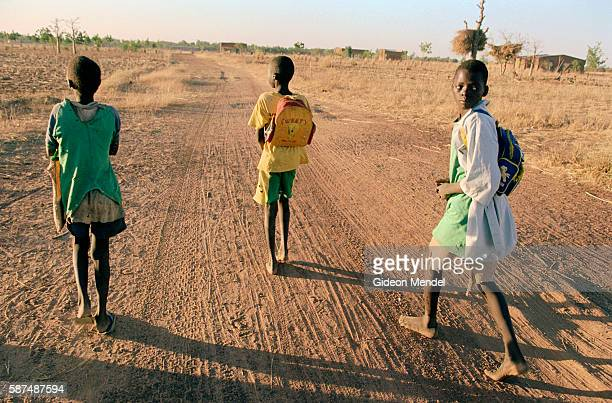 Three orphans from the Porgo household on their way to school in a remote village on the edge of the Sahara desert A communitybased programme in the...