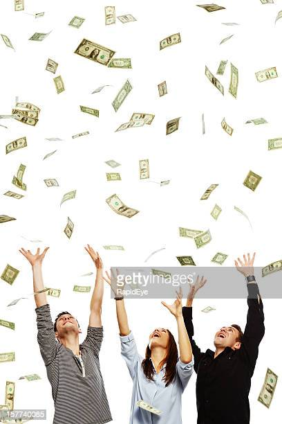 three overjoyed young adults being showered with dollars - jackpot stock pictures, royalty-free photos & images