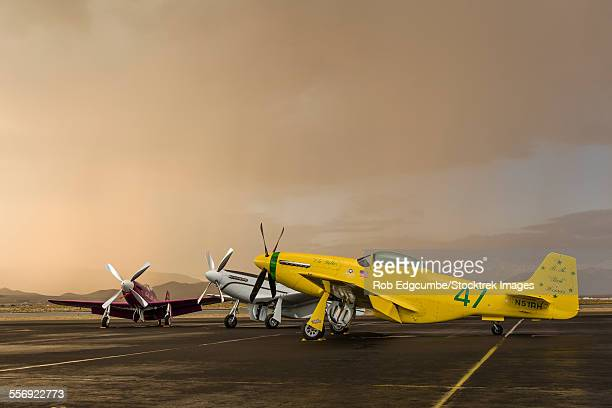 three p-51 mustangs parked on the ramp ahead of a storm at stead field, nevada. - p 51 mustang stock photos and pictures