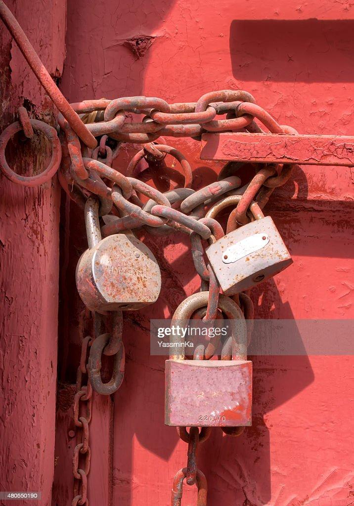 Três cadeados na porta vermelha : Foto de stock