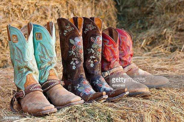 Three pair of cowboy boots sit on hay