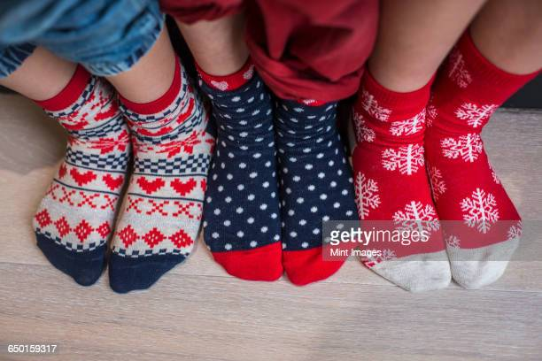 Three pairs of childrens feet in bright patterned Christmas socks.