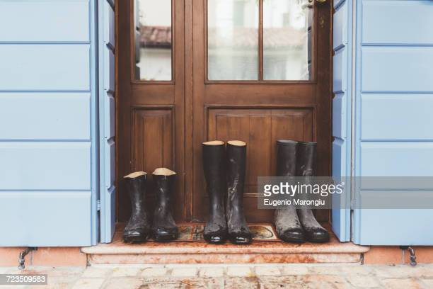 three pairs of rubber boots on doorstep - stiefel stock-fotos und bilder