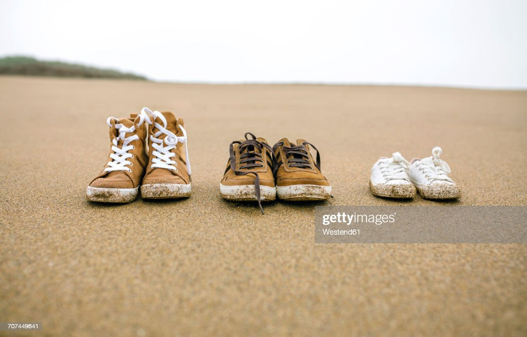 87ab349a5a9c9 Three Pairs Of Shoes With Different Sizes On The Beach Stock Photo ...