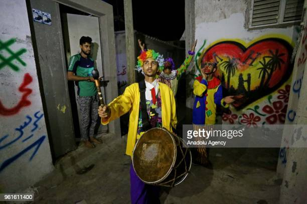 Three Palestinian men wearing clown costumes walk the Gaza City streets with their drums to wake people for predawn meal of sahur the last meal...