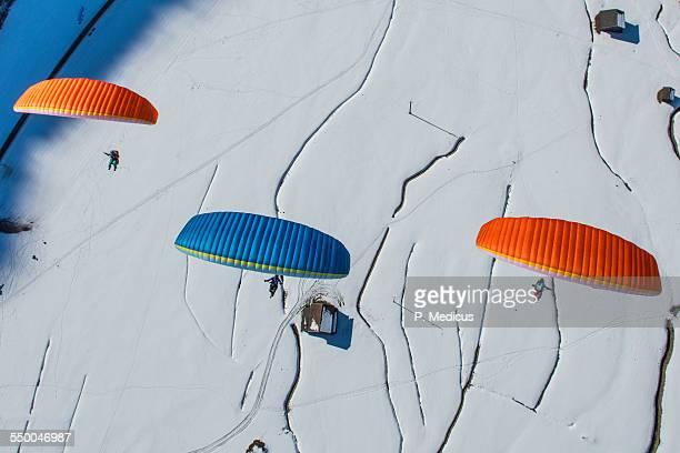 Three paragliders above winter landscape