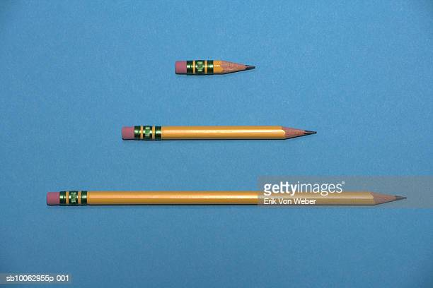 Three parallel pencils of different size against blue background, studio shot