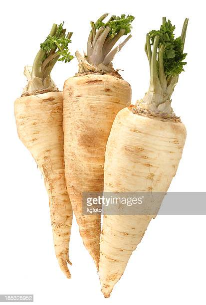 Three parsnips in front of white background