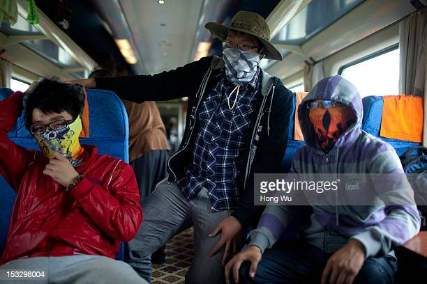 Three passengers wear masks in a train carriage of from Beijing to Lhasa on August 15 2012 in Damxung China After QinghaiTibet Railway went into...