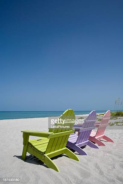 Three pastel colored beach chairs on sand at beach