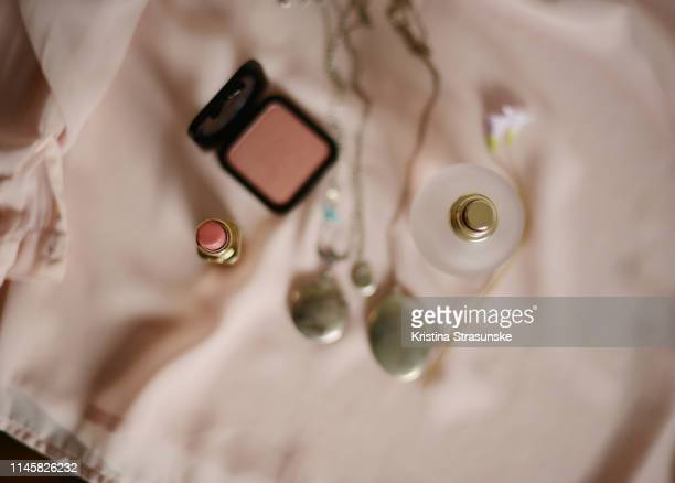 three pendant necklaces, a blusher, pink lipstick and a flower on a pink blouse - silver blouse stockfoto's en -beelden