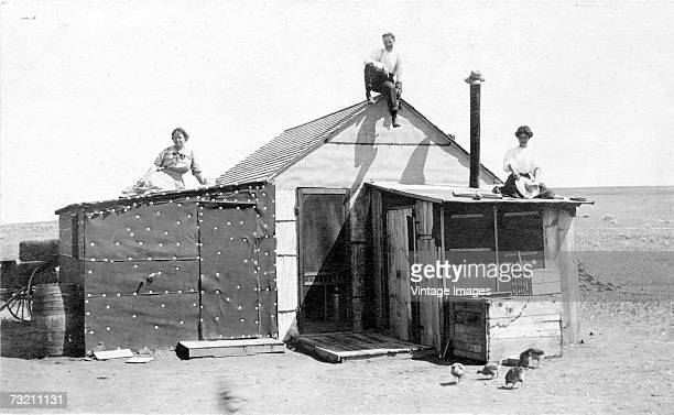 Three people a man and two women sit on the roof of a claim shack somewhere on the Great Plains in the American midwest early 1910s The structure...
