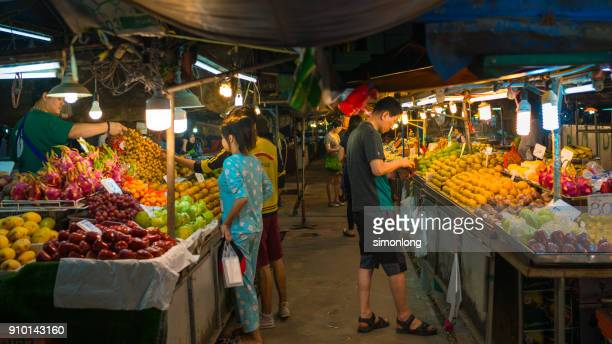 Three people are buying fruits at Maharaj Market, Krabi