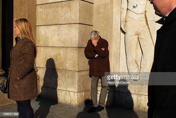 Three people are featured against a wall made of beige stone. There are the shadows of passersby on the wall and there is a human figure carved in...