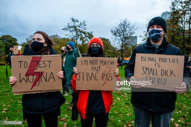 Three people are holding placards in solidarity with Polish women, during the protest against the abortion ban In Poland, that took place in The...