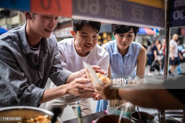 three people are ordering food at a street food counter. - taiwan stock pictures, royalty-free photos & images