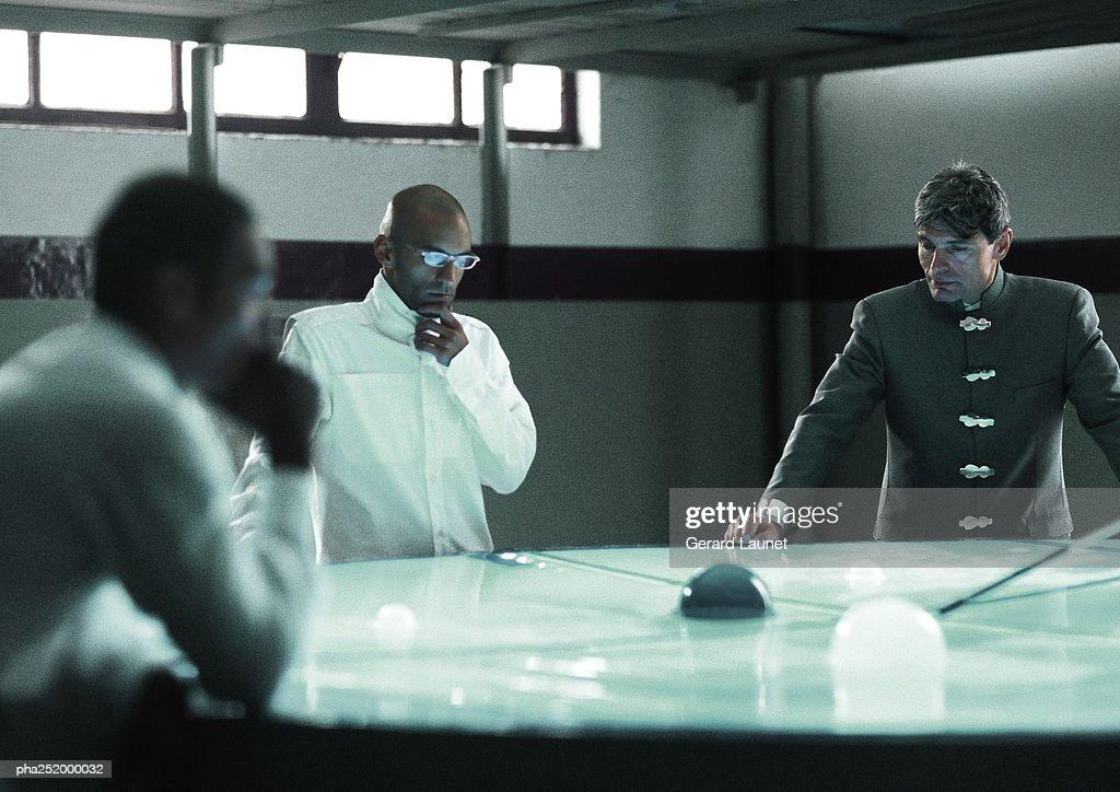 Three people around table : Stockfoto