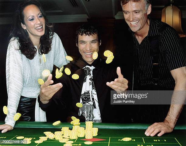 three people at casino table, young man throwing gambling chips in air - clubkleding stockfoto's en -beelden