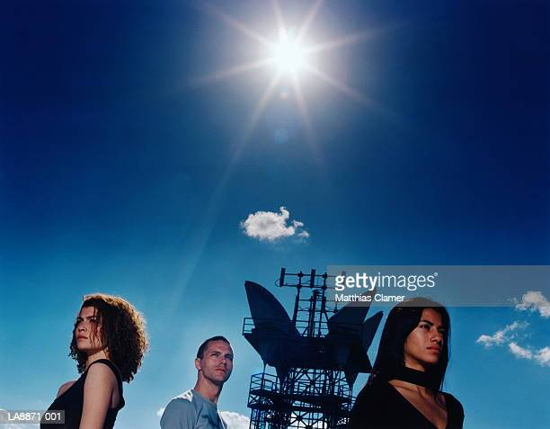 Three people by microwave transmission tower