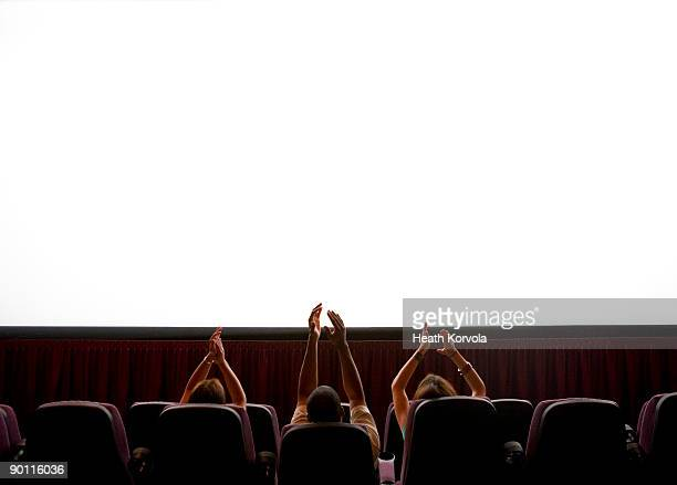Three people clapping at blank screen in theater.
