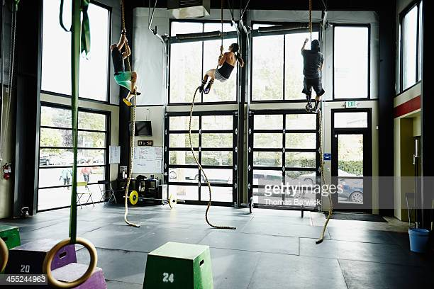 Three people climbing ropes in Gym gym