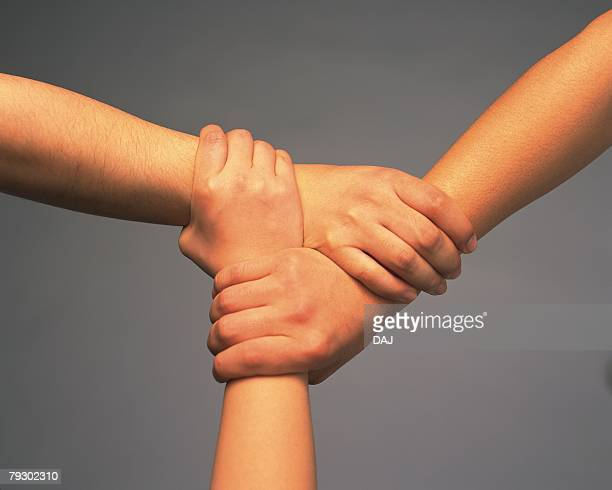 Three people connecting hands, high angle view