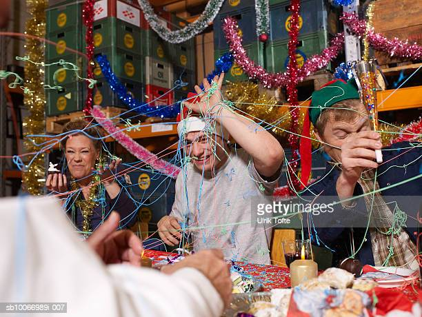 Three people covered in party streamers laughing at charismas table in warehouse
