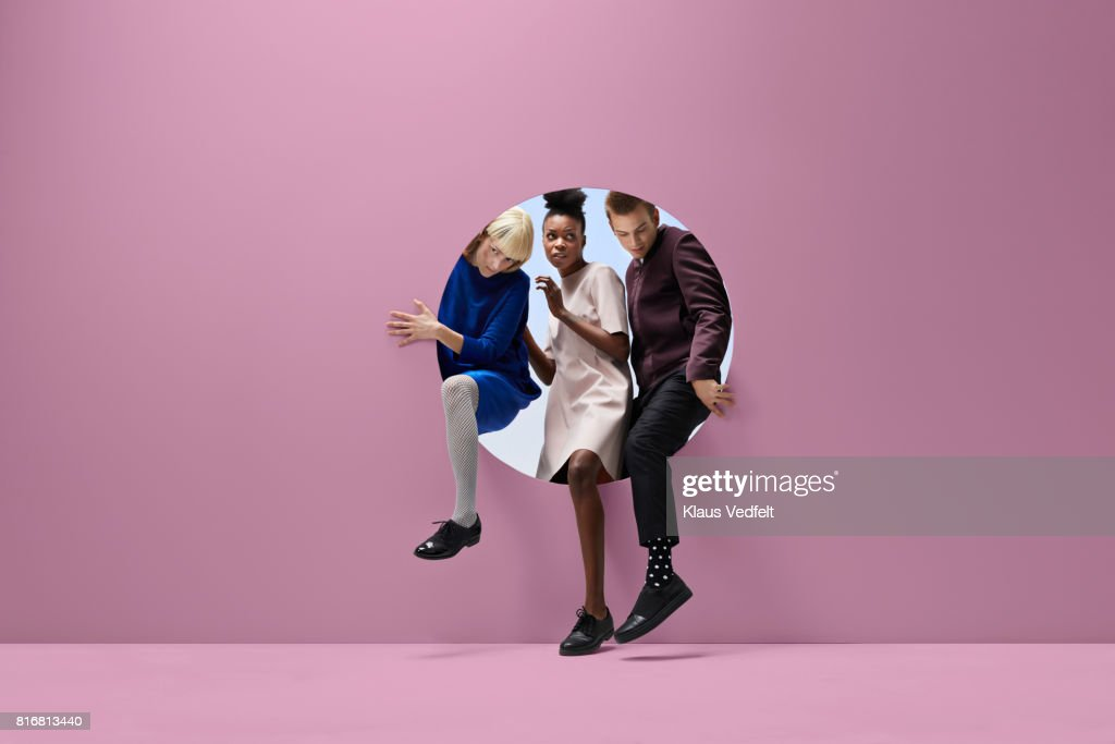 Three people crawling out of round opening in coloured wall : Stockfoto