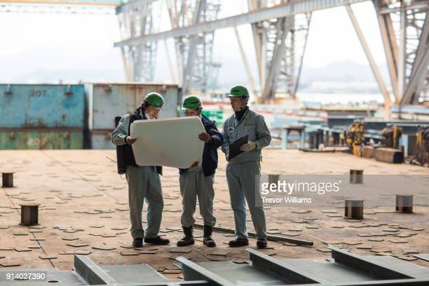 three people discussing blueprints or building plans in a shipbuilding factory - ジャンプスーツ ストックフォトと画像