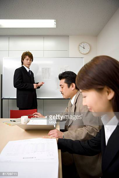 Three people discussing in meeting room