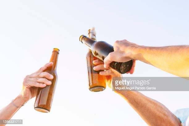 three people doing celebratory toast with beer bottles on beach at sunset, oliva, valencia, spain. - stock photo - celebratory toast stock pictures, royalty-free photos & images