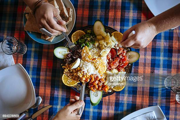 Three people eating Moroccan salad together, partial view
