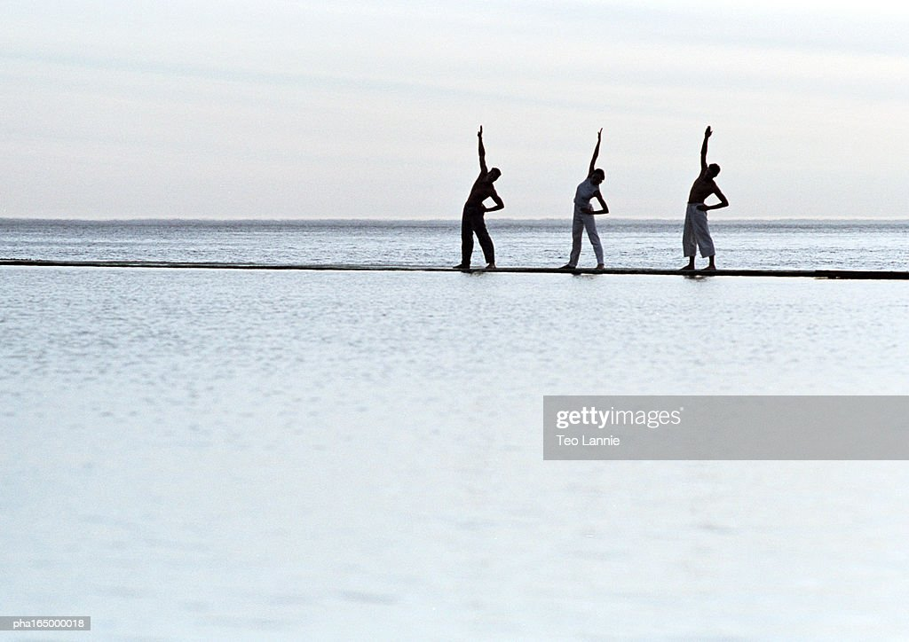 Three people exercising by the sea. : Stockfoto