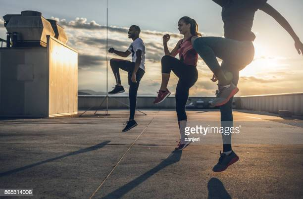 three people exercising outdoors - warming up stock pictures, royalty-free photos & images
