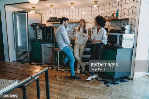drie mensen die een koffiepauze hebben op kantoor. ze drinken yerba mate samen. - koffiepauze stockfoto's en -beelden