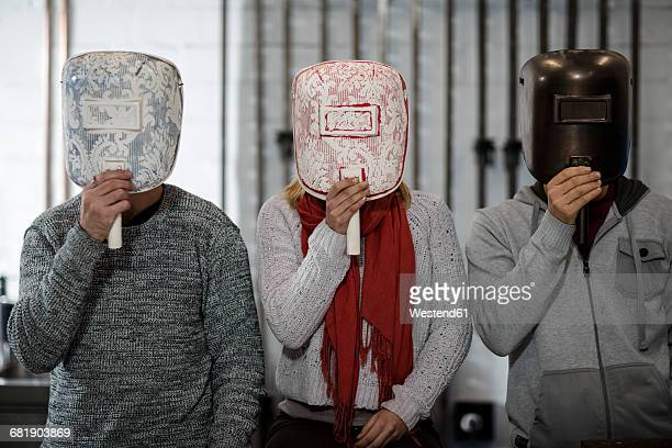 Three people hiding behind designer masks