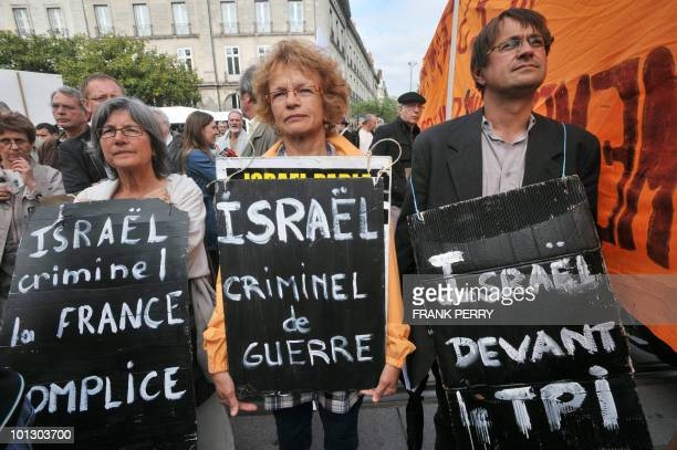 Three people hold antiIsraeli placards in the French western city of Nantes on May 31 2010 during a demonstration against Israel's deadly raid on an...