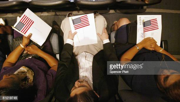 Three people hold U.S. Flags as they wait to be sworn in as American citizens at a naturalization ceremony on the Intrepid Sea-Air-Space Museum July...