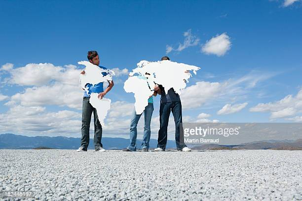 Three people holding continents