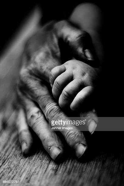 three people holding hands together - main noir et blanc photos et images de collection